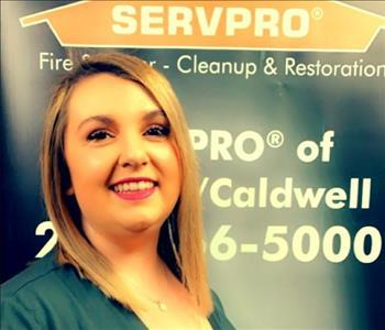 female employee standing in front of a SERVPRO sign