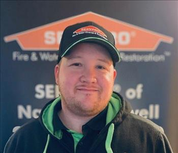 male employee standing in front of a SERVPRO sign