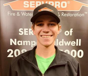 male employee wearing a black SERVPRO hat and jacket