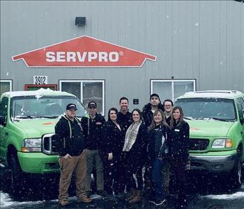 group of employees standing in front of 2 SERVPRO trucks in the snow