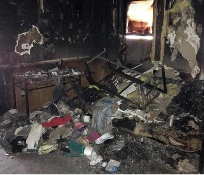 a room completely covered in soot and smoke damage after a fire with debris everywhere