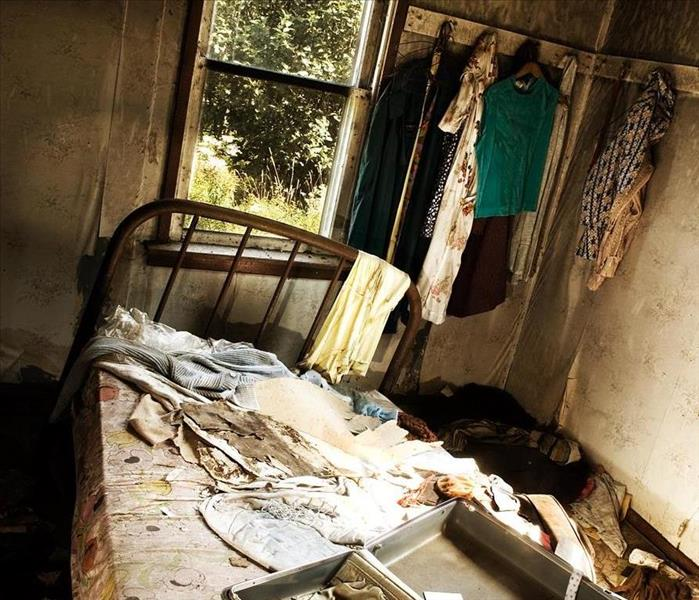 A bedroom with smoke and fire damage.