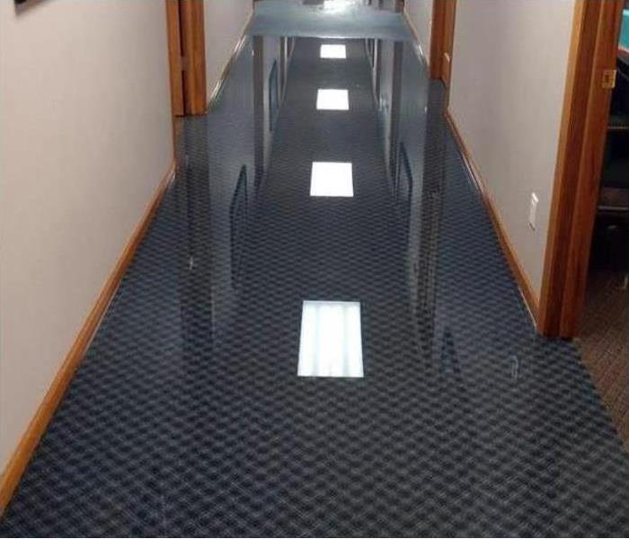A long hallway with soaked carpet needing restoration