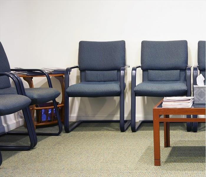 Upholstered blue chairs sitting on carpeted floor in waiting room