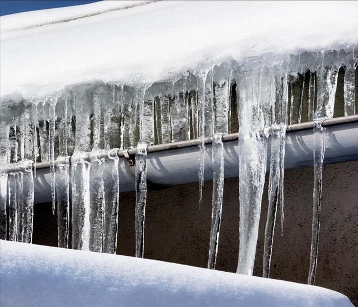 icicles hanging from a roof gutter, many